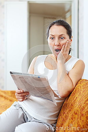 Amazed mature woman looks newspaper