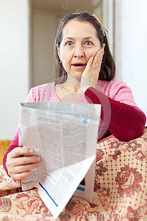 Amazed mature woman with newspaper