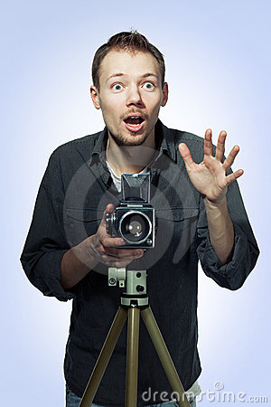 Amazed photographer with retro camera