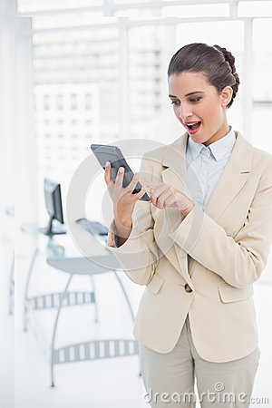 Amazed smart brown haired businesswoman using a calculator