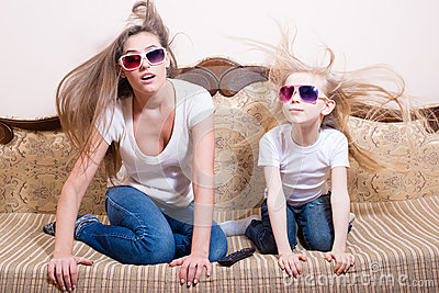Amazed young beautiful woman with blond little girl sitting watching 3D movie in 3D glasses with real life special effects