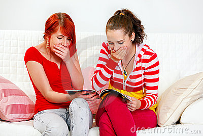 Amazed young girlfriends watching fashion magazine