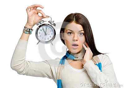 Amazed young woman with alarm clock