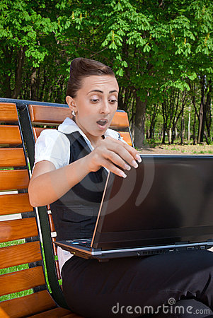 Amazed young woman with laptop sitting on bench