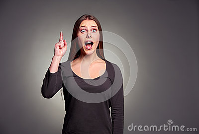 Amazed young woman pointing upward
