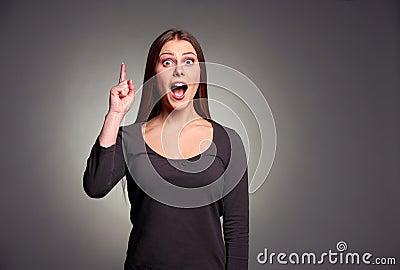 Amazed young woman pointing upward