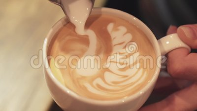 Amazing barista tutorial of making art latte, shape of a swan. Female hands, portrait. Inside shooting. Cafe business. Coffee industry. Mourning routine stock video footage