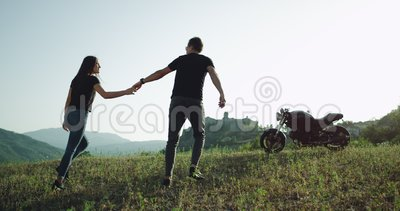In amazing beautiful landscape young couple arrived with their motorcycle and exploring the place in a summer hot day. In amazing beautiful landscape young stock footage