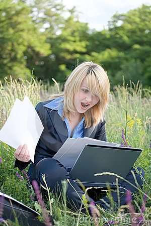 Amazing businesswoman on grass with documents