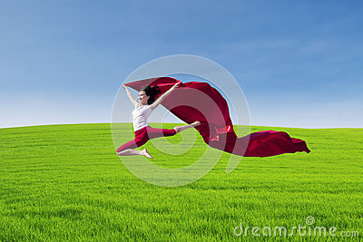 Amazing dancer jumping with red scarf on field
