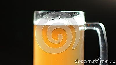 Ambacht koud bier in mok met schuim en luchtbellen roteren geïsoleerd bij studio zwarte achtergrond stock videobeelden