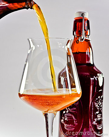 Amber beer pouring into glass from a bottle