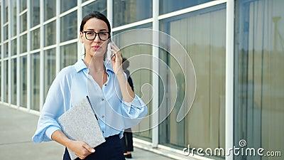Ambiciosa mujer de negocios hablando por teléfono móvil al aire libre caminando en la ciudad metrajes