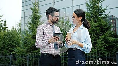 Ambitieuze ondernemers bespreken zaken buiten en werken met tablet stock video
