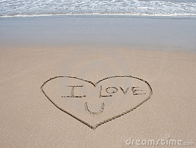 Ame o símbolo do coração na areia na praia tropical