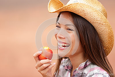 American cowgirl eating peach