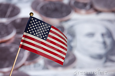 American flag over US banknotes and coins.