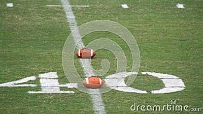 American footballs on pitch