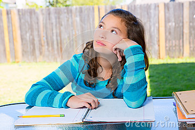 American latin teen girl doing homework on backyard