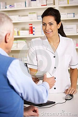 American pharmacist dispensing to senior man