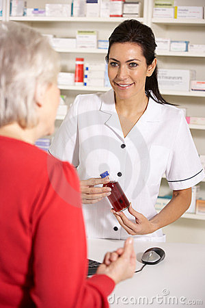 American pharmacist dispensing to senior woman