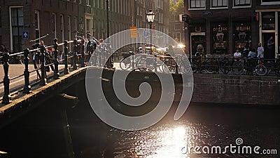 Amesterdam, die Niederlande, im Mai 2018: Schöner Sonnenuntergang in der Stadt Solargreller glanz im Wasser, Fahrräder parkte weg stock video