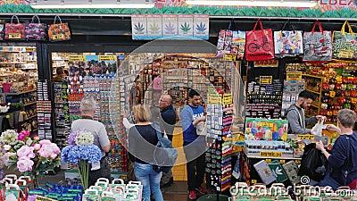 Amesterdam Nederländerna, Maj 2018: Besökare väljer blommor, och souvenir på den berömda blomman marknadsför i Amsterdam lager videofilmer
