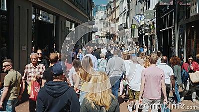 Amesterdam, Nederland, Mei 2018: Een levendige straat met veel winkels, koffie en boutiques Een menigte van toeristen gaat stock footage