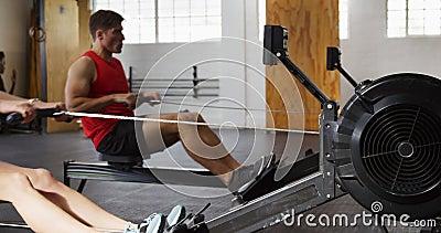 Amici caucasici atletici che si allenano su una macchina per remare archivi video