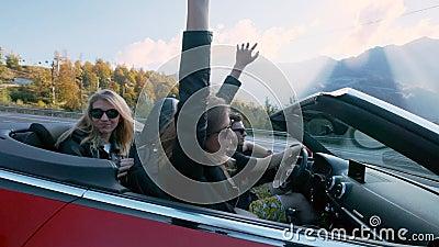 Amici femminili europei attraenti che cantano, ballanti ed applaudenti conducendo automobile senza coperchio di lusso lungo le al archivi video