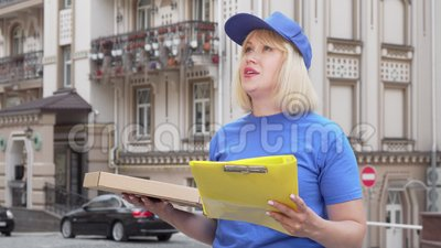 Amigable mujer de reparto de pizza sonriendo a la cámara mientras trabaja en la ciudad almacen de video