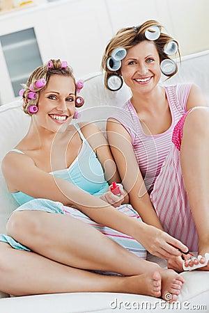 Amigos alegres con los rodillos del pelo que hacen pedicure