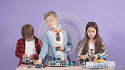 Amigos caucasianos crianças estudando engenharia, robótica, tentam montar robôs vídeos de arquivo