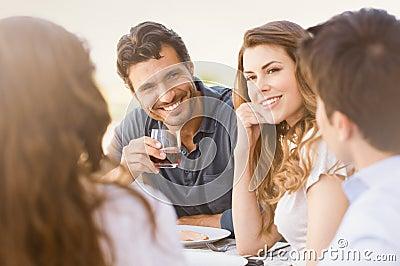 Amigos felizes que apreciam o jantar