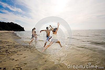 Amigos felizes que têm o divertimento pela praia