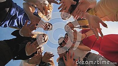 Amigos felizes se juntam em um círculo em um dia ensolarado e acenam suas mãos filme