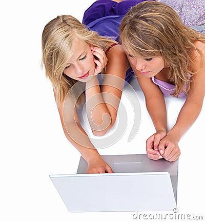 Amigos jovenes hermosos que miran la computadora portátil