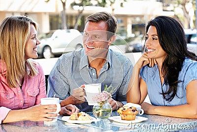 Amigos que charlan fuera del café
