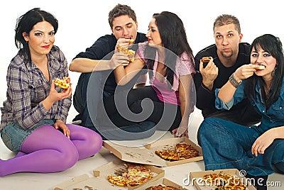 Amigos que comen la pizza