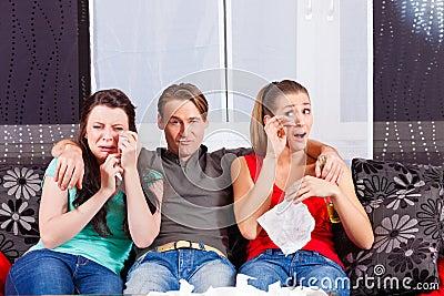 Amigos que miran una película triste en la TV