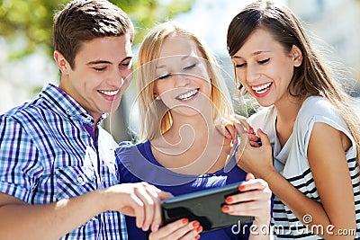 Amigos que olham a tabuleta digital