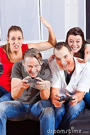 Amigos que sentam-se na frente da caixa do console do jogo