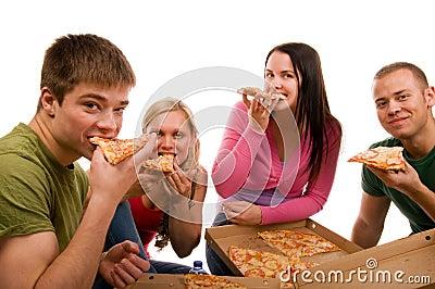 Amigos que têm o divertimento e que comem a pizza