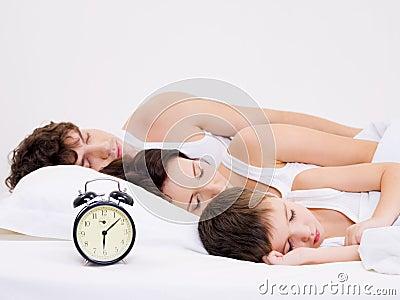 Amily sleeping with alarm clock near  their  heads