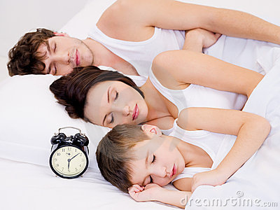 Amily sleeping with alarm clock near  their  heads