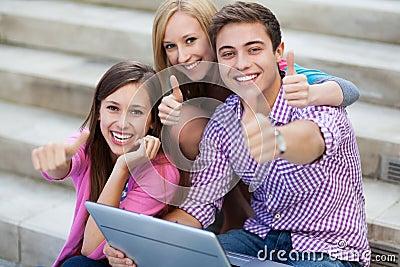 Amis avec l ordinateur portatif affichant des pouces vers le haut
