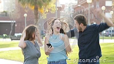 Amis enthousiastes sautant après vérification du contenu de téléphone banque de vidéos
