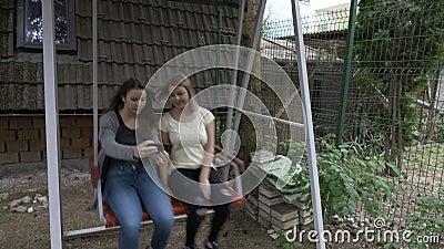 Amis féminins adolescents prenant un selfie avec le smartphone tandis qu'ils détente extérieure de oscillation ensemble dans le b banque de vidéos