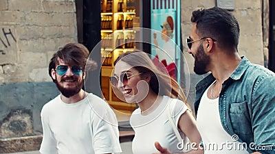 Amis multi-ethniques marchant sur la rue banque de vidéos