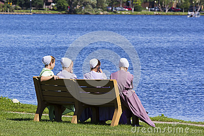 Amish girls sitting by the lake Editorial Stock Photo